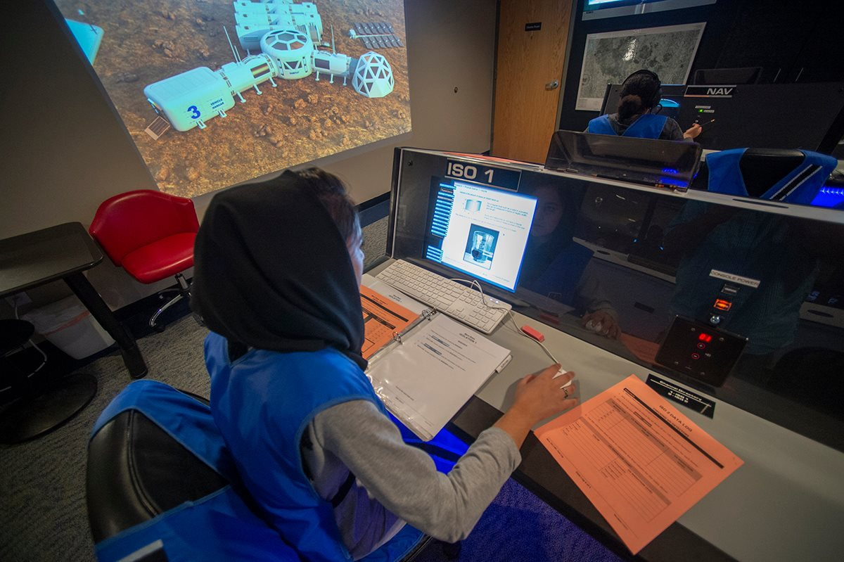 A student works at a high tech computer desk, examining Mars rover data, with a projection of a Mars rover on a large screen to the left.