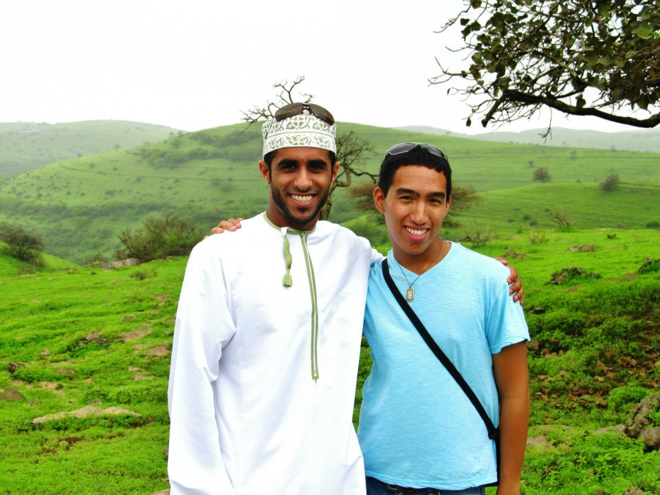 Carlo posing with a friend in Oman outdoors, in front a bright, green field.