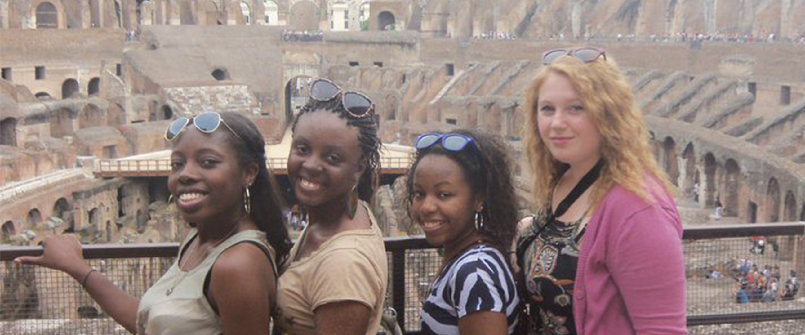Erica with study abroad friends posing at the Coliseum