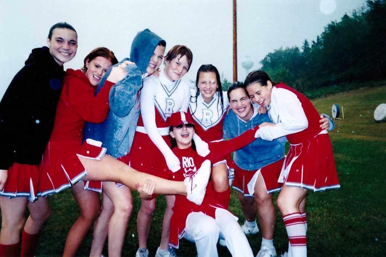 Maria, during her high school exchange, posing with her cheerleading squad on a sports field