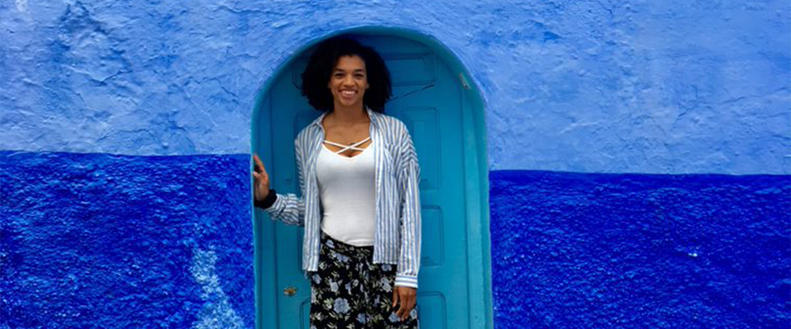 Michael posing in front of one of the blue doors in Morocco, during her study abroad experience