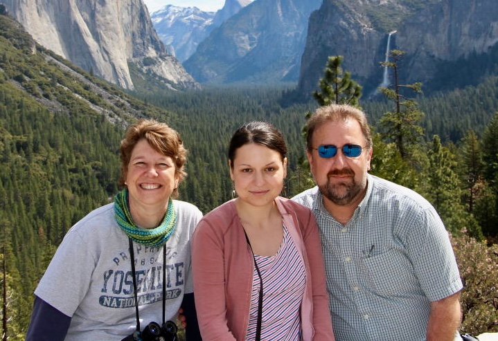 Brian and Sheila Green, smiling with their first fellow, Anna, at Yosemite National Park