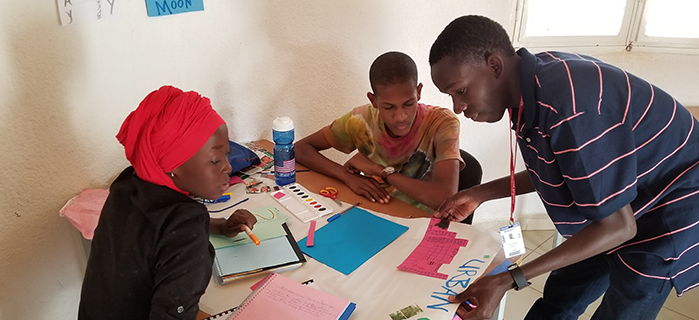 Moustapha (standing, right) helps students with a project during the English Workshop in Senegal