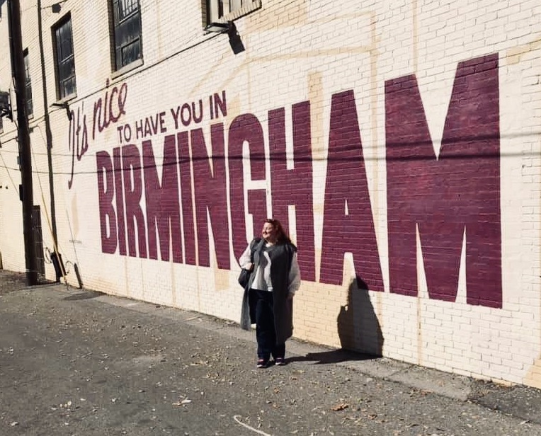 "Tetiana posing in front of a graffiti wall that reads: ""It's nice to have you in Birmingham."""