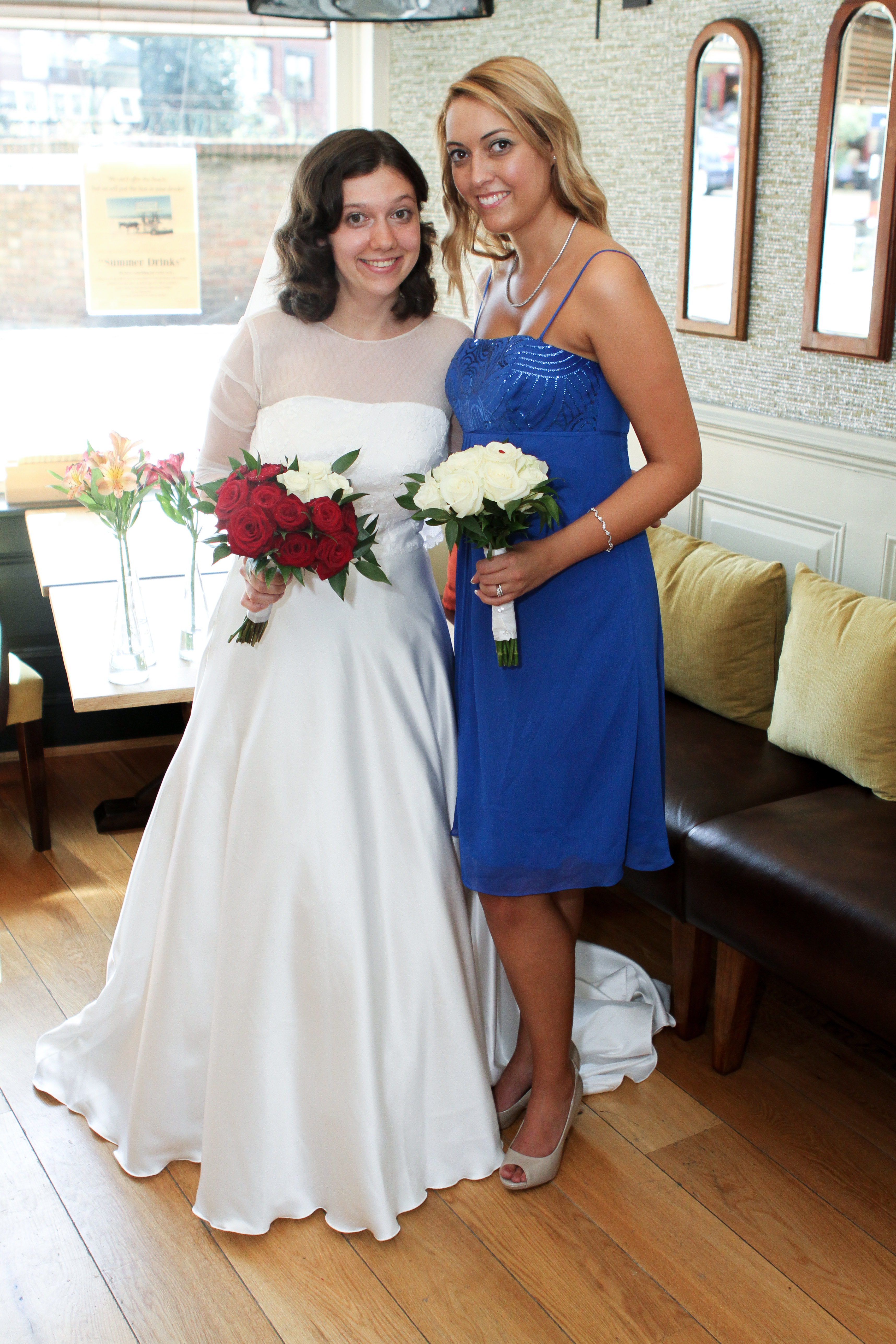 Tatyana in her wedding dress, smiling alongside bridesmaid, Laura