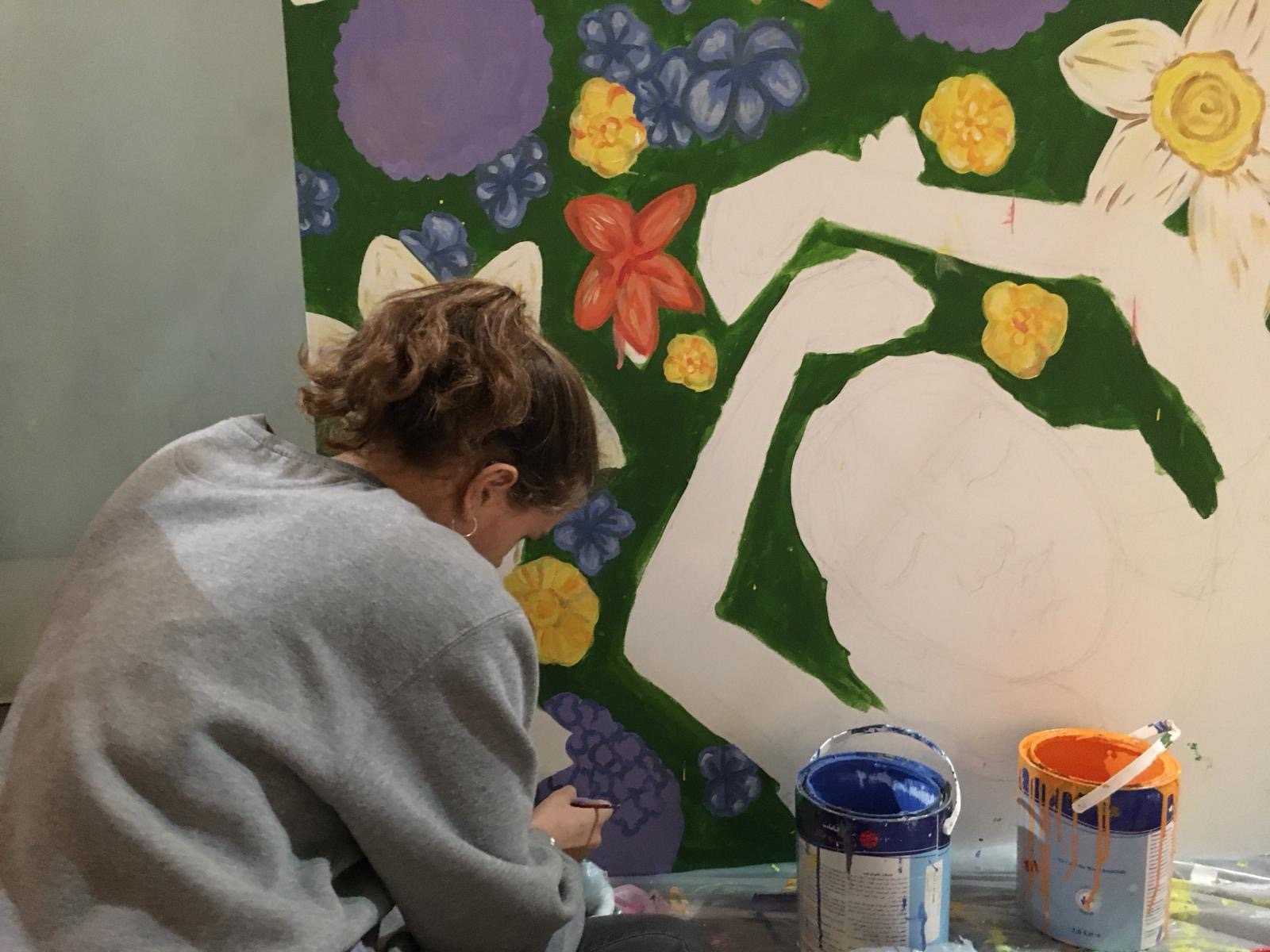 Phoebe sits on the ground, bent over a section of a mural she created at the mall. It depicts a woman laying in a field of flowers, her arms stretched above her head.