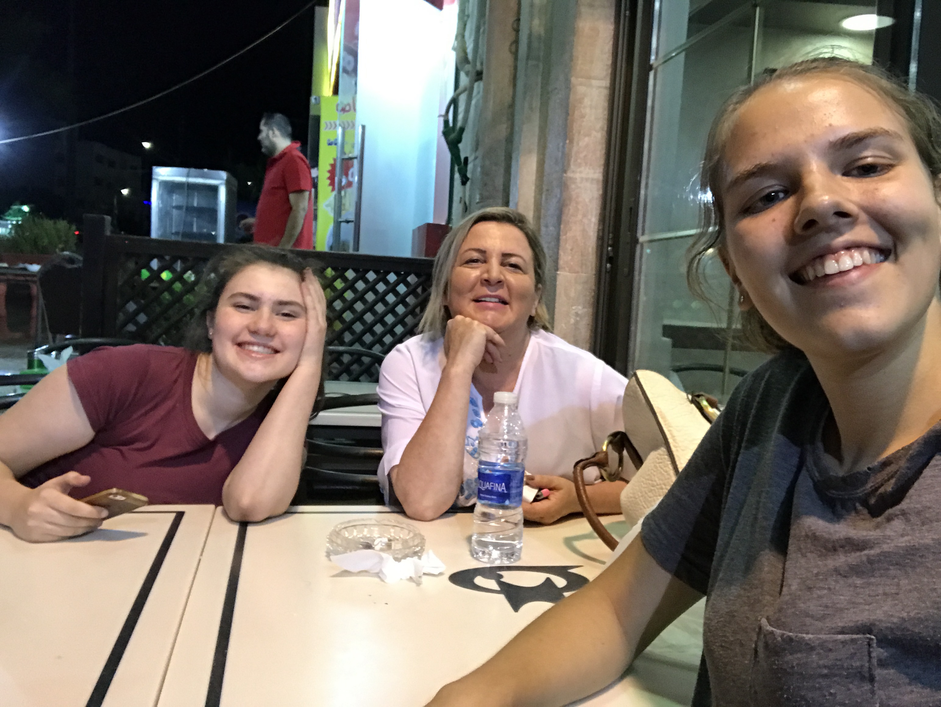 Phoebe smiles in this selfie shot, seated at an outdoor table with her host mom and another YES Abroad student.