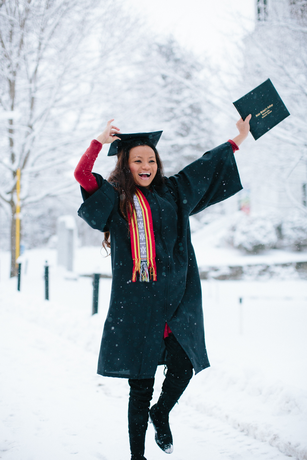 Raina, wearing a cap and gown, dancing in the snow with her diploma