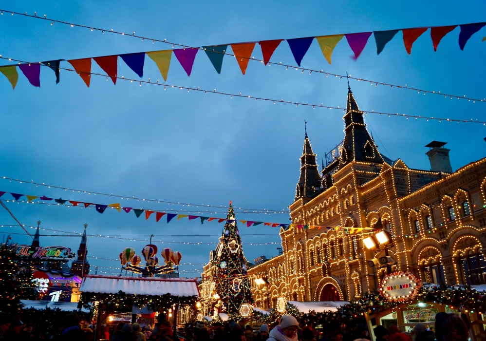 A large, stone building lit up with white, string lights, is the back drop to a holiday market in a Russian city