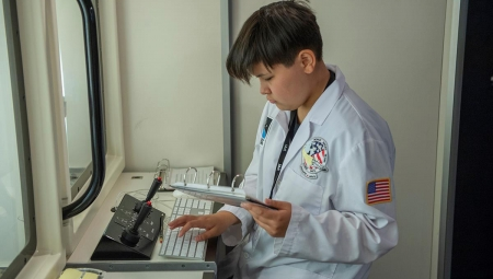 Student, dressed in a white lab coat with NASA patches, sits at a keyboard and joystick in front of a simulation screen, consulting a page in a binder.