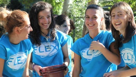 A group of young women wearing light blue FLEX T-shirts, laugh and smile at the camera