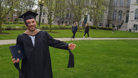 Egzon, dressed in a graduation cap and gown, poses on the lawn of his university.