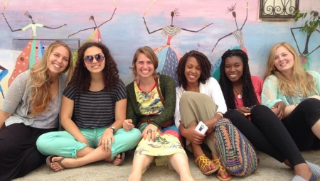A group of young women sit against a colorful wall, smiling and relaxing