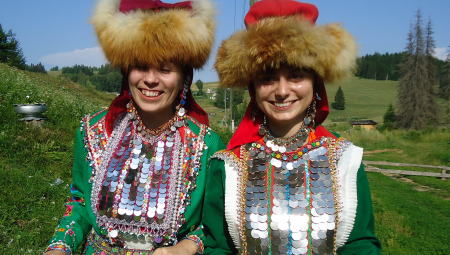 Two women wearing traditional dress, including fur hats, pose together on a hillside