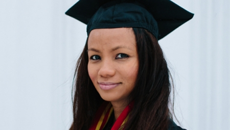 Raina, wearing a cap and gown, smiles at the camera in this portrait shot