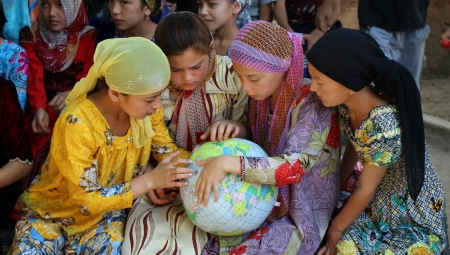 Tajik girls gather around a globe to explore the countries
