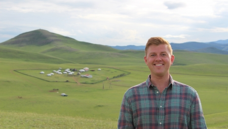 Chris smiles, standing in front of rolling green hills