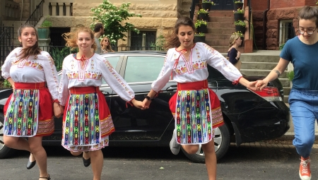 Hannah, wearing Converse sneakers and jeans, dances alongside three young Bulgarian girls wearing traditional folk costume