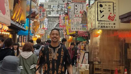 Elias, posing on a street in Japan, during his 2014 study abroad experience
