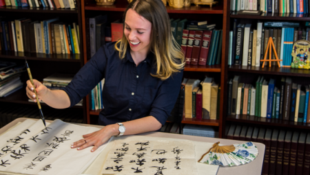 Leigh Lawrences practices her Chinese calligraphy skills with a smile, paintbrush in hand